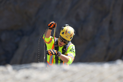 A scaler preparing to rappel down the cliff face. Photo credit: Gina Anderson